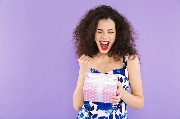 Retrato de uma jovem bonita, segurando a caixa de presente isolada, comemorando