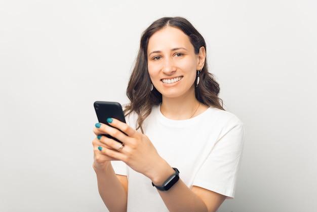 Retrato de uma jovem bonita sorridente alegre segurando um smartphone e olhando para a câmera