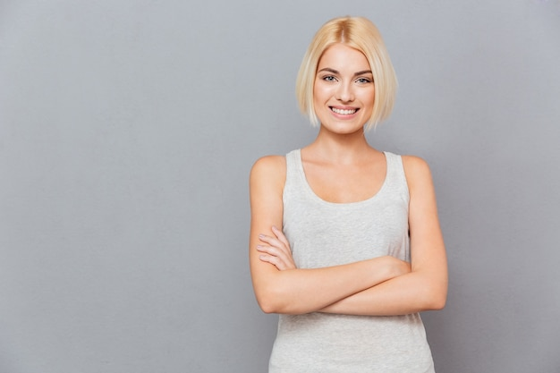 Retrato de uma jovem bonita sorridente em pé com os braços cruzados sobre uma parede cinza