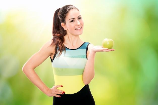 Retrato de uma jovem bonita sorridente feliz em roupas de ginástica com maçã