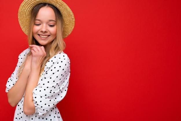 Retrato de uma jovem bonita sorridente hipster loira com vestido de verão na moda e chapéu de palha. sexy