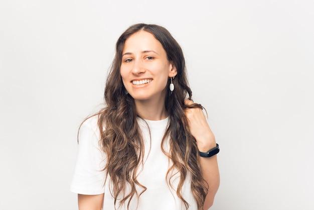 Retrato de uma jovem bonita sorrindo e olhando para a câmera sobre fundo branco