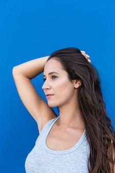 Retrato de uma jovem bonita sorrindo e posando com uma parede azul ao fundo