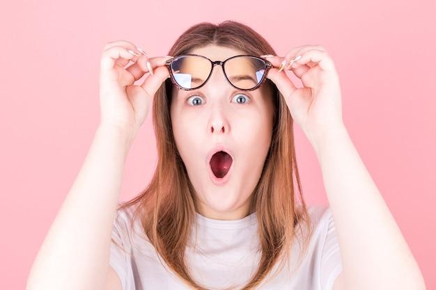 Retrato de uma jovem bonita surpresa em óculos, olhando para frente enquanto levantava os óculos