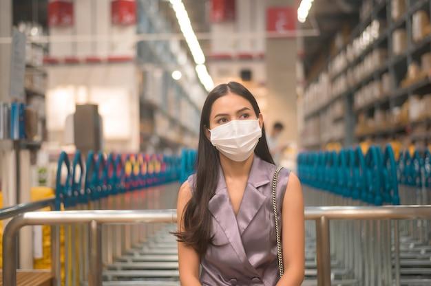 Retrato de uma jovem bonita usando uma máscara cirúrgica em um shopping center, covid-19 e o conceito de pandemia