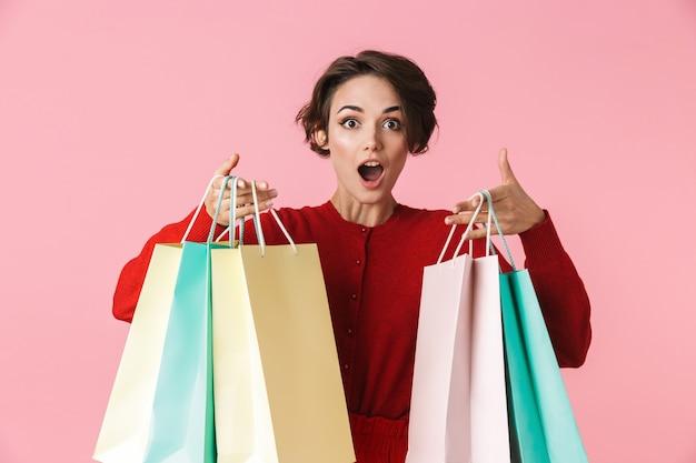 Retrato de uma jovem bonita vestindo roupas vermelhas, isolado, carregando sacolas de compras