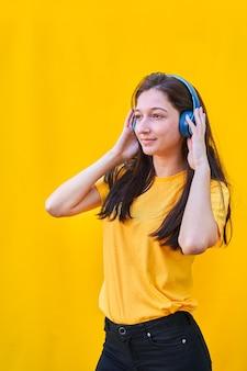 Retrato de uma jovem branca com longos cabelos castanhos, camiseta amarela e calça jeans preta, ouvindo música com seus fones de ouvido azuis.