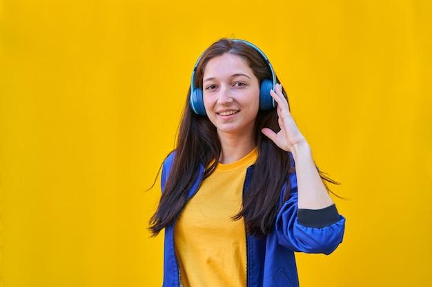 Retrato de uma jovem branca com longos cabelos morenos, jaqueta azul e calça jeans preta, ouvindo música com seus fones de ouvido azuis.