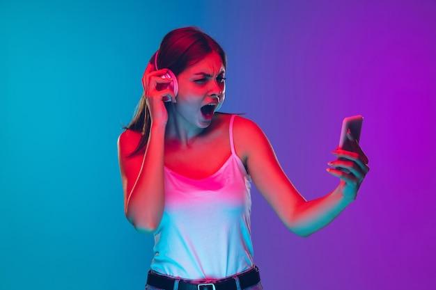 Retrato de uma jovem branca isolado em um fundo gradiente roxo-azulado com luz de néon