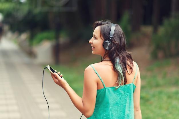 Retrato de uma jovem brilhante em roupas de verão, ouvindo música com fones de ouvido, mantendo o telefone móvel na grama através das palmeiras. conceito de liberdade.