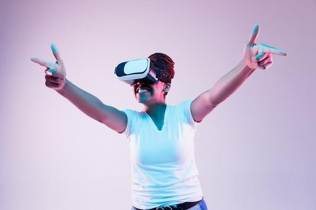 Retrato de uma jovem brincando com óculos vr em luz de néon em gradiente
