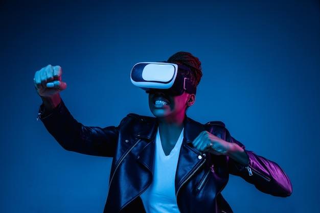 Retrato de uma jovem brincando com óculos vr em luz de néon no azul