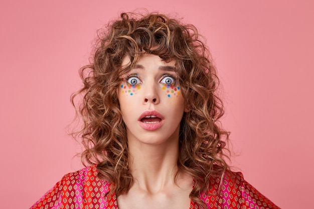 Retrato de uma jovem cacheada chocada com olhos e boca bem abertos, isolada, vestindo roupas listradas de rosa e laranja