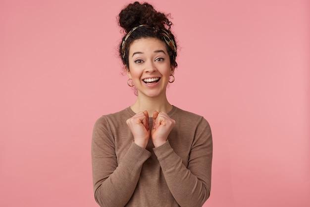 Retrato de uma jovem cacheada feliz, sorri amplamente, alegra-se, colocando as mãos no peito, olhando para a câmera isolada sobre o fundo rosa.