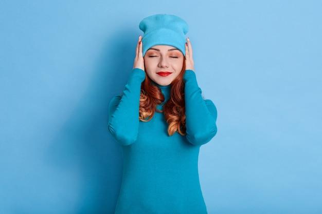 Retrato de uma jovem calma vestindo um suéter casual e boné, mantendo os olhos fechados e cobrindo as orelhas com os braços