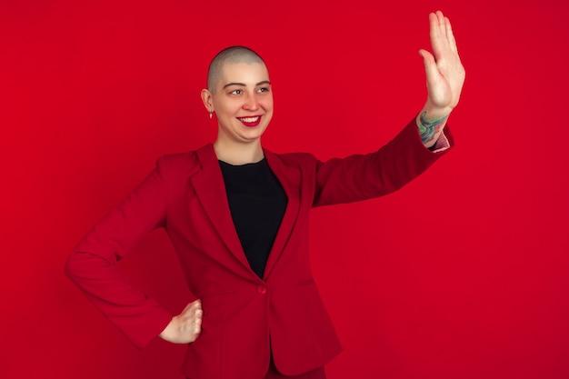 Retrato de uma jovem careca caucasiana na parede vermelha