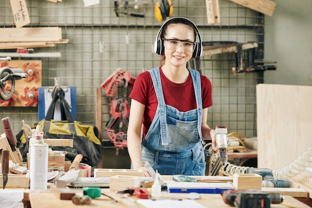 Retrato de uma jovem carpinteira com protetores de ouvido e óculos, trabalhando com grampeador pneumático ao fazer móveis