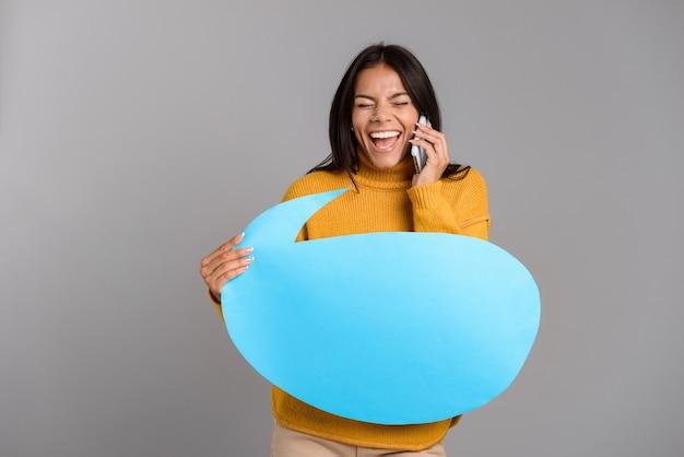 Retrato de uma jovem casual alegre isolada sobre uma parede cinza, falando no celular, mostrando um balão de fala em branco