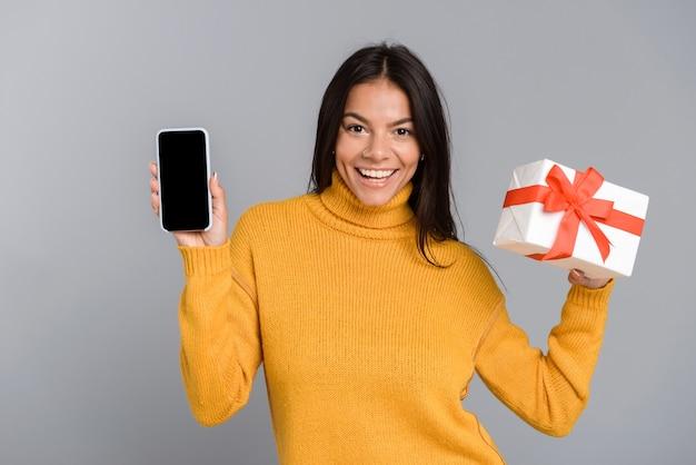 Retrato de uma jovem casual alegre isolada sobre uma parede cinza, mostrando a tela do celular em branco, segurando uma caixa de presente