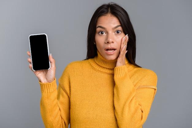 Retrato de uma jovem casual chocada isolada sobre uma parede cinza, mostrando uma tela em branco do celular