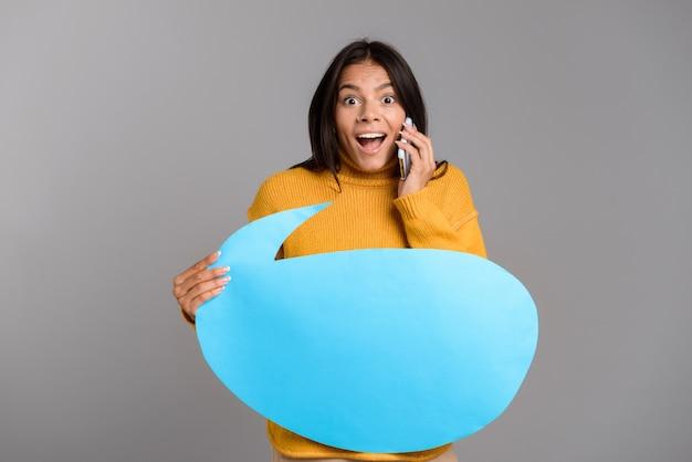 Retrato de uma jovem casual e animada isolada sobre uma parede cinza, falando no celular, mostrando um balão de fala em branco