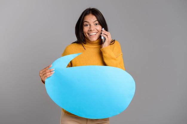 Retrato de uma jovem casual feliz isolada sobre uma parede cinza, falando no celular, mostrando um balão de fala em branco