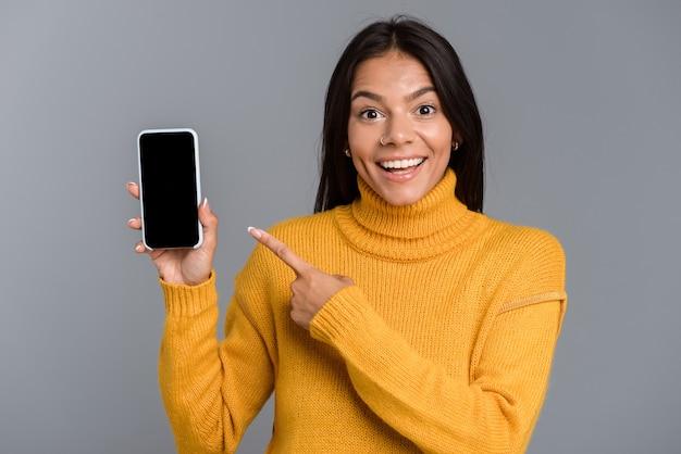 Retrato de uma jovem casual feliz isolada sobre uma parede cinza, mostrando a tela do celular
