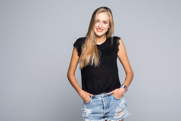 Retrato de uma jovem casual segurando os polegares nas alças de sua calça jeans enquanto sorria para a câmera em um fundo cinza