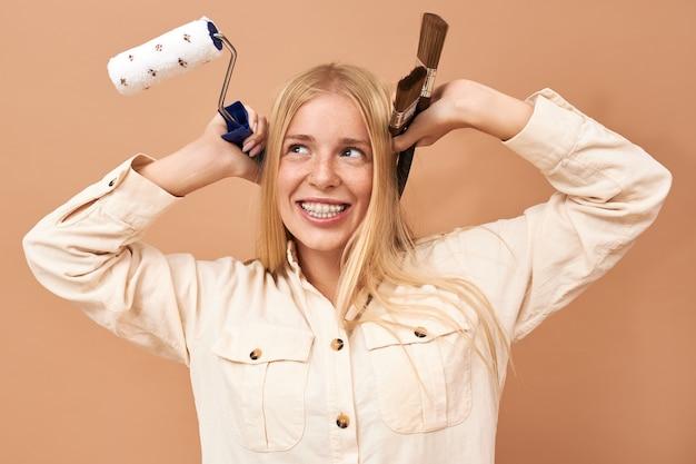 Retrato de uma jovem caucasiana animada segurando um pincel e um rolo enquanto pinta as paredes do quarto