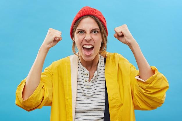 Retrato de uma jovem caucasiana de sucesso feliz com chapéu vermelho e capa de chuva amarela, regozijando-se com a vitória, sucesso ou boas notícias positivas com os punhos cerrados, aplaudindo, gritando de alegria