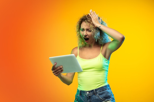 Retrato de uma jovem caucasiana em fundo gradiente de estúdio em néon