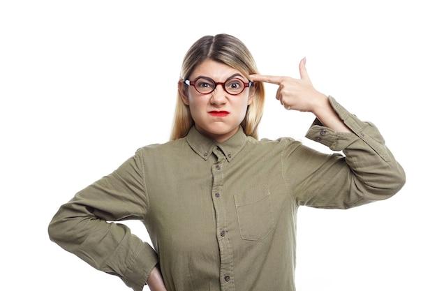 Retrato de uma jovem caucasiana frustrada com raiva, usando óculos, apontando o dedo indicador para a têmpora, como se estivesse segurando uma pistola, vai se atirar enquanto se sente estressada com muitos dever de casa