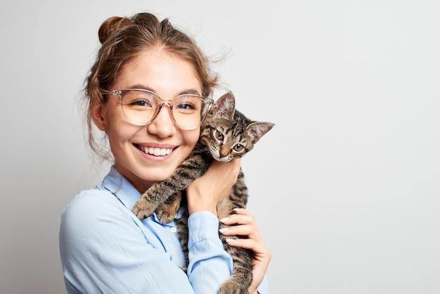 Retrato de uma jovem cazaque asiática sorridente e alegre, brincando com um gatinho