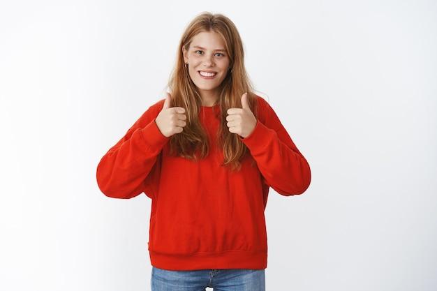 Retrato de uma jovem charmosa totalmente concorda, sorrindo amplamente, mostrando um gesto de polegar para cima para dar uma resposta positiva, gostando da boa ideia, torcendo, apoiando em pé em um suéter vermelho aconchegante e aconchegante