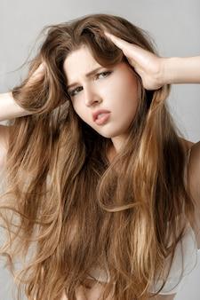 Retrato de uma jovem chateada com cabelo comprido.