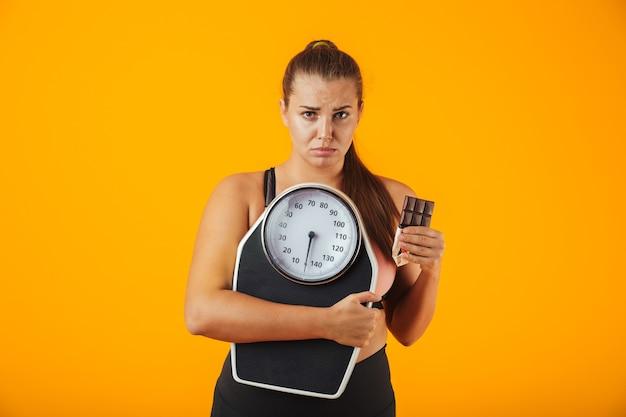Retrato de uma jovem chateada com excesso de peso, vestindo roupas esportivas, em pé, isolado na parede amarela, segurando uma barra de chocolate e balanças