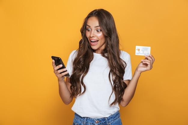 Retrato de uma jovem chocada com longos cabelos castanhos em pé sobre uma parede amarela, segurando um telefone celular, mostrando um cartão de crédito de plástico