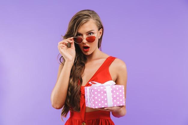 Retrato de uma jovem chocada em posar de vestido vermelho