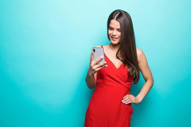 Retrato de uma jovem chocada num vestido olhando para o celular isolado sobre a parede azul