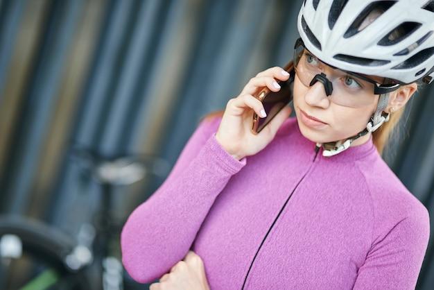 Retrato de uma jovem ciclista mulher esportiva, usando equipamento de proteção, fazendo uma ligação usando