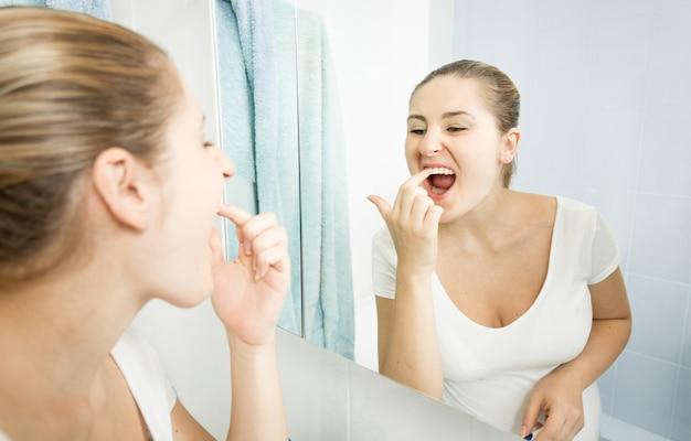 Retrato de uma jovem colhendo comida presa nos dentes com o dedo