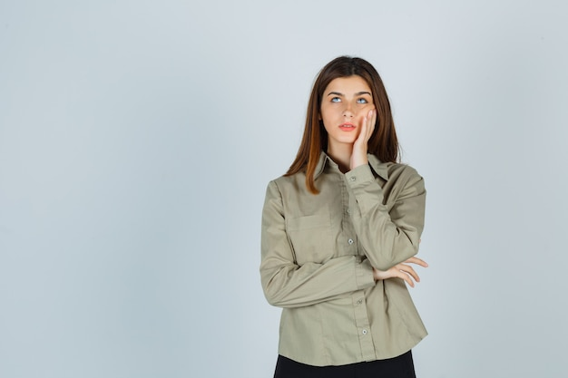 Retrato de uma jovem com a bochecha na mão enquanto olha para cima com uma camisa, saia e uma vista frontal pensativa