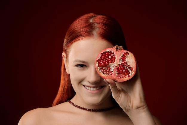 Retrato de uma jovem com cabelo ruivo e fruta romã cobrindo o rosto
