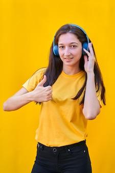 Retrato de uma jovem com cabelos castanhos compridos, camiseta amarela e calça jeans preta, ouvindo música com seus fones de ouvido azuis com o polegar para cima da mão direita