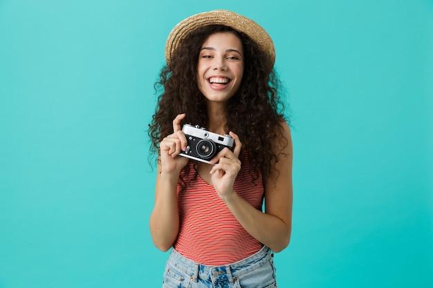 Retrato de uma jovem com chapéu de palha segurando uma câmera retro, isolada sobre uma parede azul