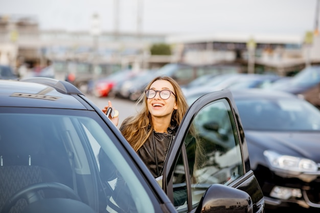 Retrato de uma jovem com contrato de locação ao ar livre no estacionamento perto do aeroporto