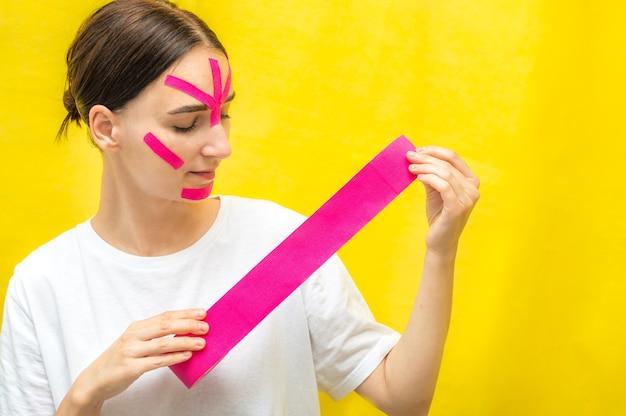 Retrato de uma jovem com fitas de kinesio no rosto.