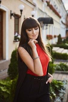 Retrato de uma jovem com maquiagem brilhante em uma roupa elegante na rua da cidade