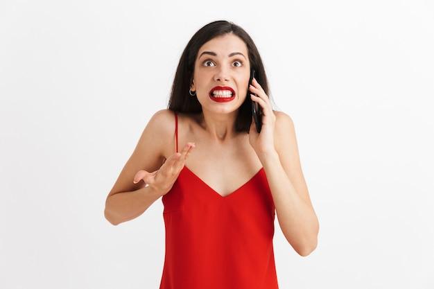 Retrato de uma jovem com raiva em um vestido isolado, falando no celular