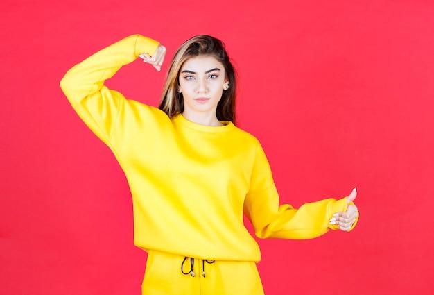 Retrato de uma jovem com roupa amarela em pé e levantando os polegares